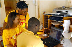 Photo of Tuskegee University Students working in a solar powered home office in their 2002 Solar Decathlon house.